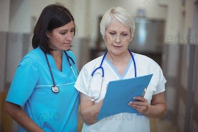 Female surgeon and nurse having discussion over file in corridor