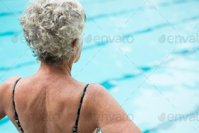 Senior woman looking at swimming pool