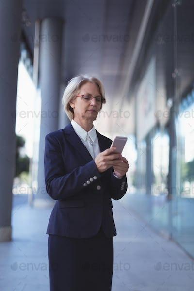 Businesswoman using smart phone outdoors