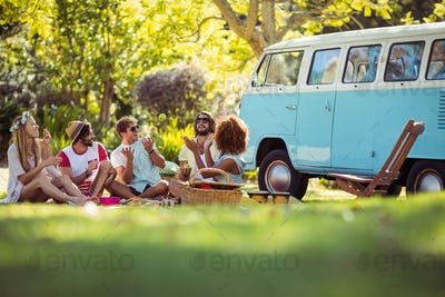 Group of friends having fun together near campervan