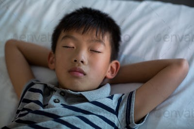 Boy sleeping on bed in bedroom