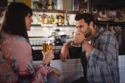 Couple interacting while having beer at counter