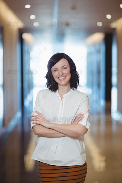 Portrait of female business standing with arms crossed in corridor