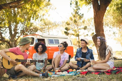 Smiling friends looking at man playing guitar while sitting on field