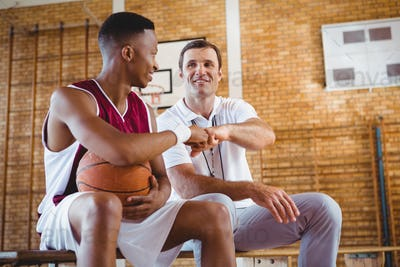Basketball player doing fist bump with coach