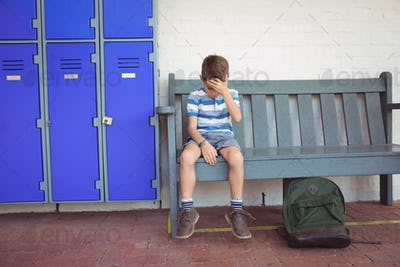 Full length of sad boy sitting on bench by lockers