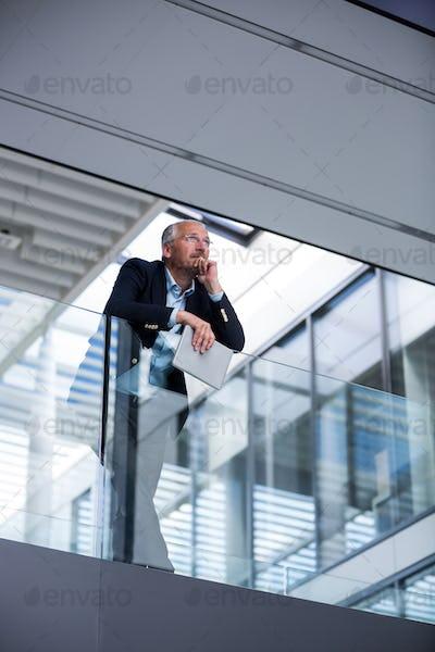 Businessman holding digital tablet at office corridor