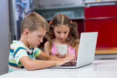 Siblings using laptop and mobile phone in kitchen