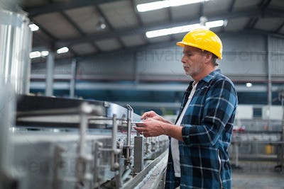 Factory worker monitoring production line