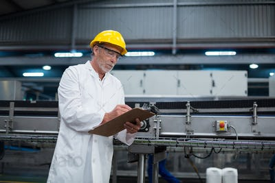Factory engineer maintaining record on clipboard in factory