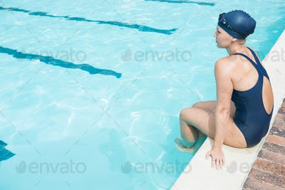 Thoughtful woman relaxing at poolside