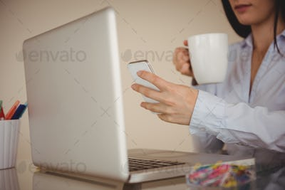 Close up of woman using smart phone while sitting by laptop