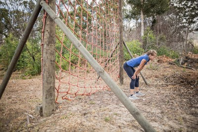 Tired woman bend down with hands on knees during obstacle course