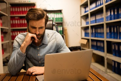 Thoughtful business executive using laptop in file storage room
