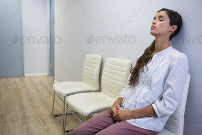 Sad patient with eyes closed sitting on chair at hospital