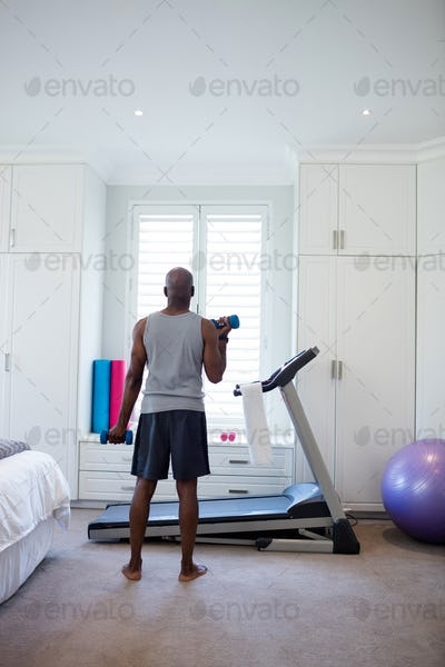 Rear view of man exercising with dumbbells in bedroom