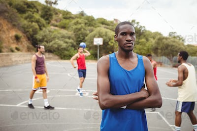 Male basketball player standing with his crossed in the court