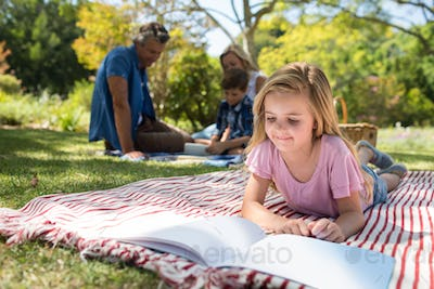 Girl lying on blanket and reading book while family sitting in background