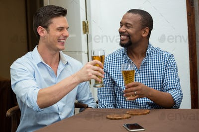 Cheerful friends toasting beer glasses in restaurant