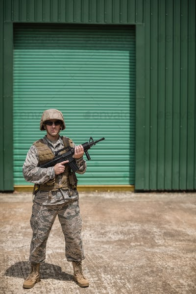 Military soldier standing with a rifle