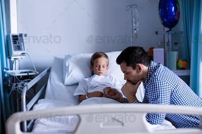 Depressed father holding his son hand