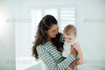 Mother holding her baby girl in the bathroom