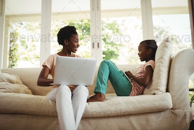 Mother and daughter using laptop and digital tablet