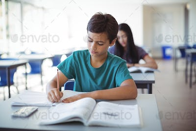 Schoolboy doing homework in classroom
