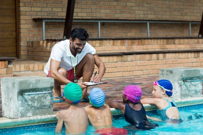 Instructor writing on clipboard while explaining little swimmers at poolside