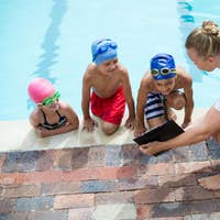 Female instructor showing clipboard to children at pool side