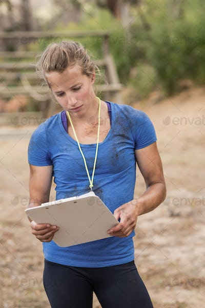 Female trainer holding clipboard during obstacle course