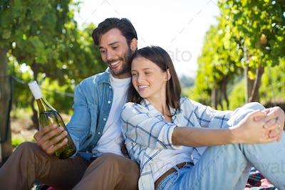 Happy couple holding wine bottle
