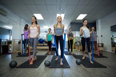 Fit women performing stretching exercise with resistance band