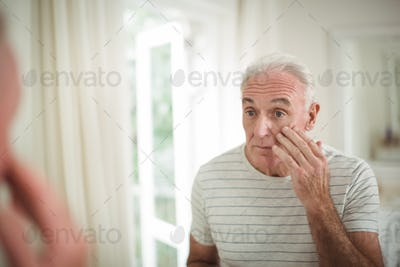 Senior man looking at mirror