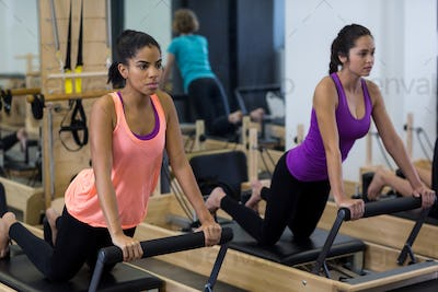 Fit women exercising on reformer