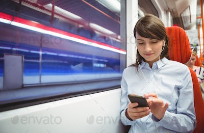 Executive using mobile phone while listening music