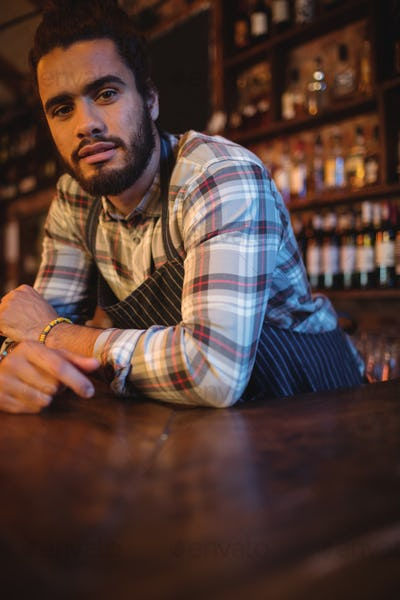 Portrait of waiter leaning at counter