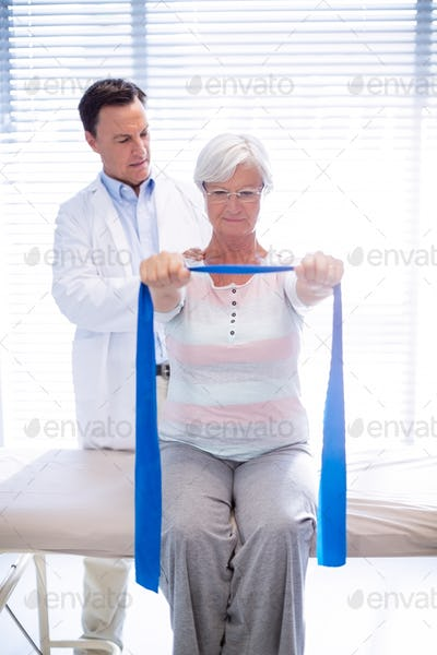 Male physiotherapist giving shoulder massage to senior woman