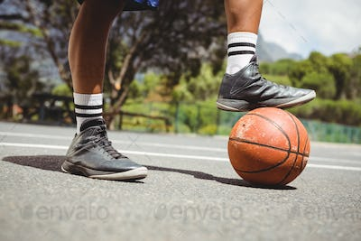 Close up of man standing with one leg on basketball