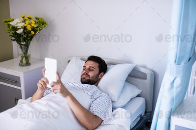 Male patient using digital tablet in the ward