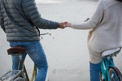 Mid section of couple holding hands on bicycle at beach