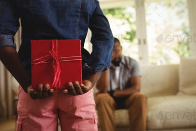 Son hiding gift behind his back for father