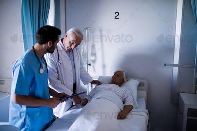 Doctors comforting senior patient on bed