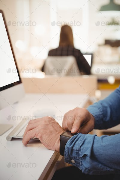 Mid section of male executive using smartwatch at desk