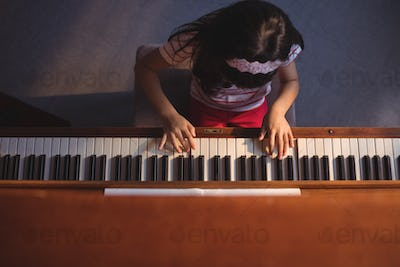 Overhead view of elementary girl playing piano in classroom