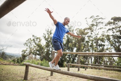 Fit man balancing on hurdles during obstacle course training