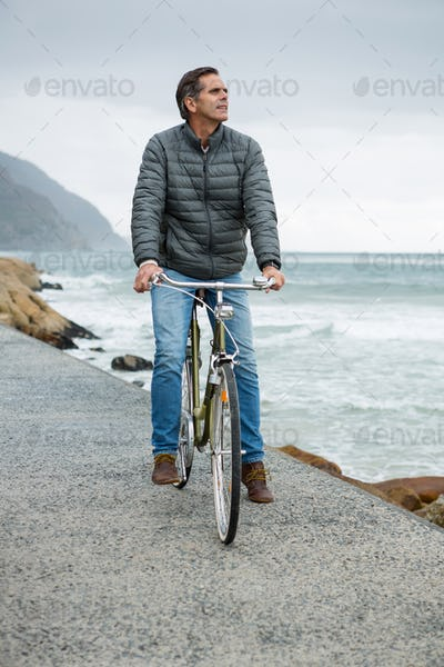 Thoughtful man standing on bicycle