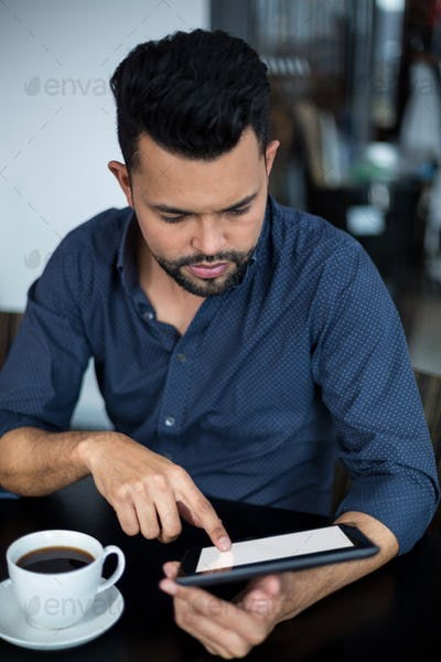 Business executive using digital tablet while having cup of tea