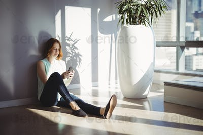 Beautiful executive sitting on floor and using mobile phone