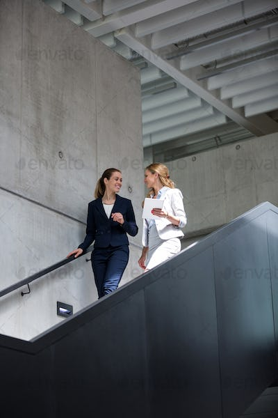 Businesswomen discussing over digital tablet while walking on staircase